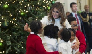 US First Lady Melania Trump hugs children in the East Room as she tours Christmas decorations at the White House in DC