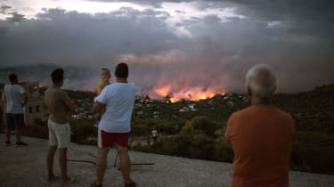 TOPSHOT - EDITORS NOTE: Graphic content / People watch a wildfire in the town of Rafina, near Athens, on July 23, 2018. - At least 20 people have died and more have been injured as wild fires