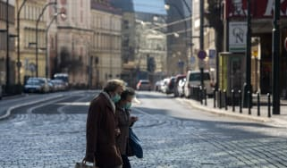 Two ladies cross the road in Prague, Czech Republic wearing face masks
