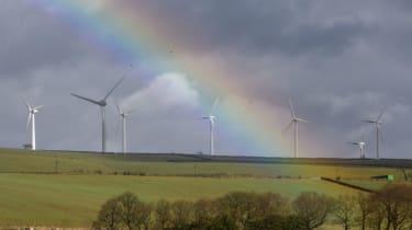 A rainbow illuminates the sky above a wind farm near Sheffield