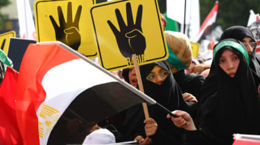 Protesters hold placards showing the 'Rabia sign' which has become the symbol of the Rabaa massacre