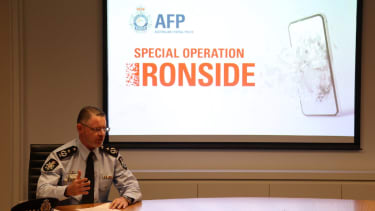 Man sitting in front of screen reading 'Operation Ironside'