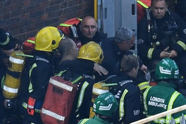 LONDON, ENGLAND - JUNE 14:A man is rescued by fire fighters after a huge fire engulfed the 24 storey residential Grenfell Tower block in Latimer Road, West London in the early hours of this m