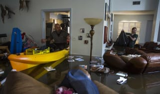 Survivors survey the damage to their flooded home in Houston