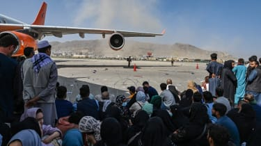 Afghan people sit as they wait to leave Kabul airport