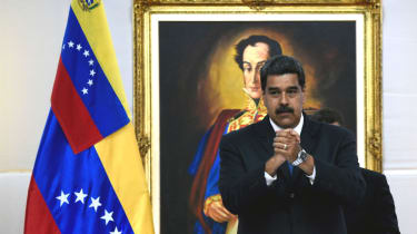 Nicolas Maduro stands in front of a portrait of Simon Bolivar in the presidential palace