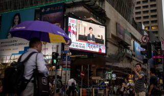 HONG KONG, CHINA - SEPTEMBER 04: People walk past a big screen replaying Hong Kong Chief Executive Carrie Lamannouncing the formal withdrawal of the extradition bill on September 04, 2019 in