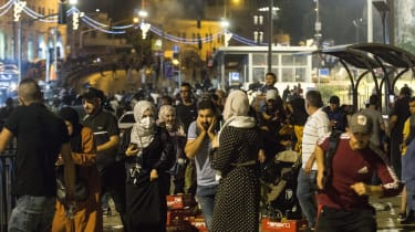 Palestinians flee from Israeli security forces near the Al-Aqsa mosque