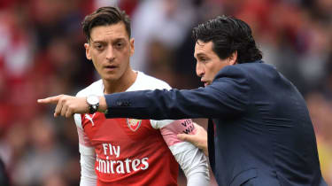 German midfielder Mesut Ozil receives instructions from Arsenal head coach Unai Emery