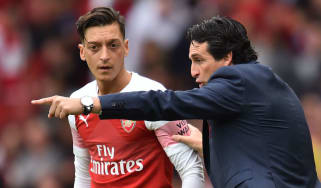 German midfielder Mesut Ozil receives instructions from Arsenal head coach Unai Emery