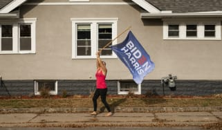 A Joe Biden supporter waves a flag outside her home.
