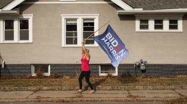A Joe Biden supporter waves a flag outside her home.