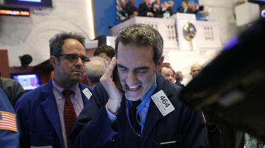 NYSE traders work the phones as the Dow Jones closes down 1,175.21 points