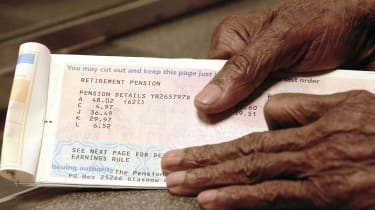 An OAP's hands holding a pension book