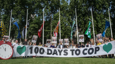 Activists hold banners and placards in Parliament Square