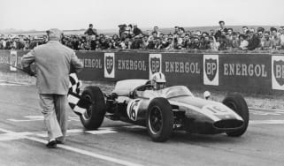 Australian racing driver Jack Brabham takes the chequered flag to win the French Grand Prix at Rheims in a Cooper-Climax T53, 3rd July 1960.(Photo by /Hulton Archive/Getty Images)