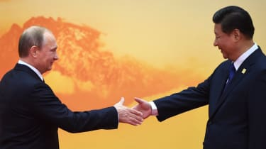 Vladimir Putin shakes hands with Xi Jinping at the Asia-Pacific Economic Cooperation summit
