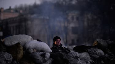 An anti-government protester smokes as he stands at a barricade in Kiev on February 6, 2014. Ukraine's unrest erupted in November 2013 after President Viktor Yanukovych rejected an associatio