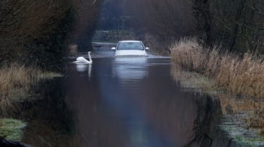 LANGPORT, UNITED KINGDOM - JANUARY 29:A car drives through flood water on the Somerset Levels on January 29, 2014 near Langport in Somerset, England. As weather forecasters predict more storm