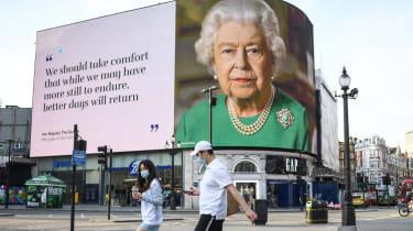 A couple wearing masks walk past an image of Queen Elizabeth II.