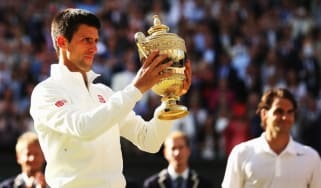 Novak Djokovic poses with the Gentlemen's Singles Trophy after defeating Roger Federer