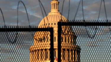 The US Capitol is seen behind a fence with razor wire.