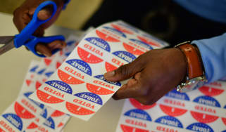 """A volunteer cuts out """"I VOTED TODAY"""" stickers for voters queueing outside a polling station"""