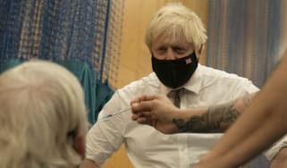 Boris Johnson watches as a booster jab is administered in Little Venice, London