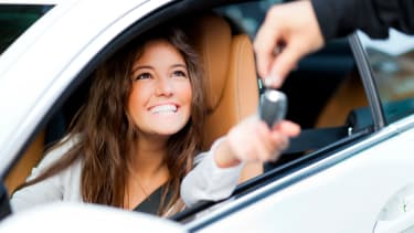 Smiling women sat in a car reaching through the open window to accept a car key