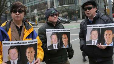 Protesters hold signs calling for the release of Canadian citizens Michael Spavor and Michael Kovrig