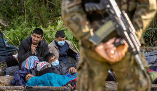 A Polish border guard stands watch over a group of migrants