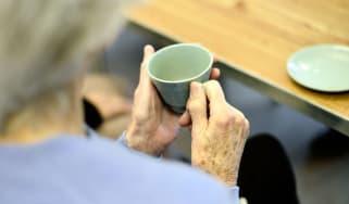 An elderly lady enjoys a cup of tea at an AgeUK Centre