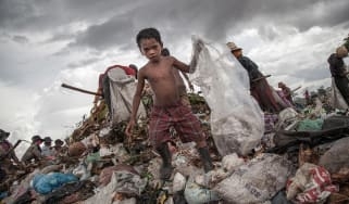 A young boy collects plastic from a landfill in Cambodia
