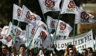 Farc members and supporters wave flags bearing the movement's new logo at its first conference as a political party