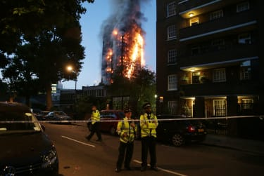 TOPSHOT - Police man a security cordon as a huge fire engulfs the Grenfell Tower early June 14, 2017 in west London. The massive fire ripped through the 27-storey apartment block in west Lond