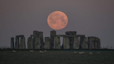 The full moon sets behind Stonehenge