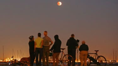 MELBOURNE, AUSTRALIA - APRIL 15:People watch as the 'Blood Moon' rises over the water in Wlliamstown on April 15, 2014 in Melbourne, Australia. The Lunar Eclipse, resulting in the Moon appear