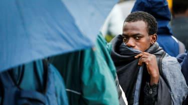 Migrants queue to enter the refugee centre near Porte de la Chapelle, northern Paris