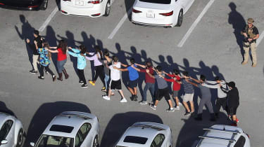 Students and staff are escorted from the school following the shooting