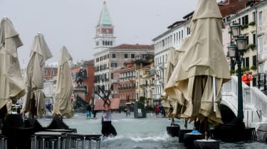 A man carries a table in the flooded Riva degli Schiavoni during a high-water (Acqua Alta) alert in Venice on October 29, 2018. - The flooding, caused by a convergence of high tides and a str