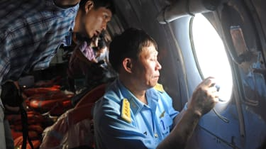 This picture taken from aboard a flying Soviet-made AN-26 used as a search aircraft by Vietnamese Air Force to look for missing Malaysia Airlines flight MH370, shows an officer (R) and a repo