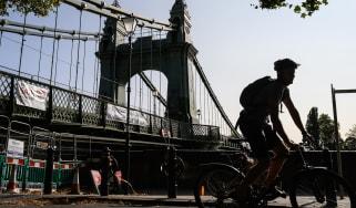 A cyclist negotiates the closed pathways around Hammersmith Bridge