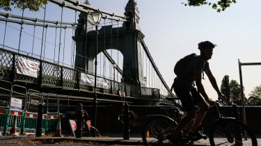 A cyclist negotiates the closed pathways around Hammersmith Bridge