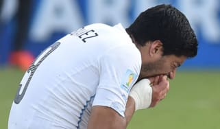 Luis Suarez puts his hand to his mouth after biting Giorgio Chiellini