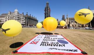 A Greenpeace protest against a third runway takes place outside Parliament on Monday