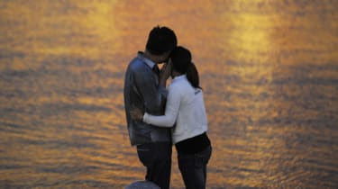 This picture taken on September 12, 2012 shows a couple embracing by a riverside in Tianjin. China's transient urban lifestyles have combined with frenetic social change, booming wealth and m
