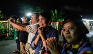 Onlookers smile as they watch an ambulance carrying boys rescued from the cave