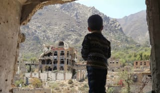 A child looking out at buildings destroyed by an air strike in Taiz, Yemen