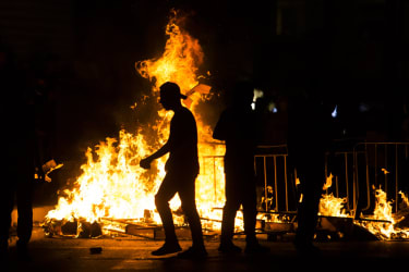 Palestinians stand by a burning barricade during clashes with Israeli police