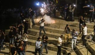 Palestinians flee a stun grenade thrown Israeli security forces near the Al-Aqsa mosque